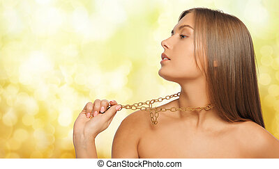 woman wearing golden necklace over yellow lights - beauty,...