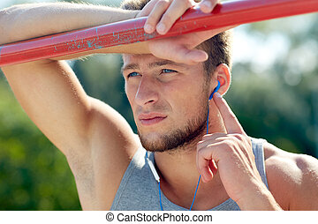 young man with earphones and horizontal bar - fitness,...