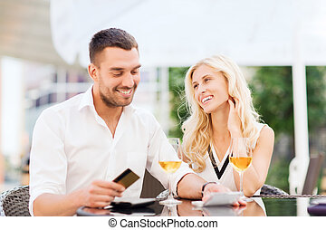 happy couple with bank card and bill at restaurant - date,...