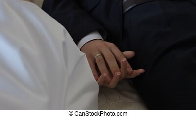 Gently connected hands of a newly-married couple with wedding rings on a finger on a background of a white wedding dress