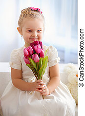 beautiful little girl in a white dress with a bouquet of...