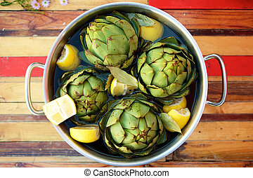 Artichokes in a pot - Top view artichokes and lemons in a...