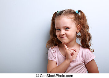 Cunning thinking small kid girl with finger near face on...