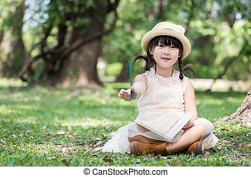 Little asian girl show pencil for writing book with smiling face in the park