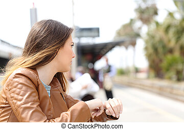 Angry girl waiting in a train station and looking to railway