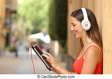 Girl browsing a tablet and listening with headphones - Happy...