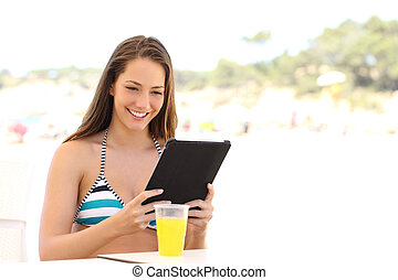 Girl reading a tablet or ebook on summer holidays in a snack...