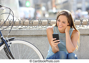 Happy girl watching media in a smart phone sitting in the...