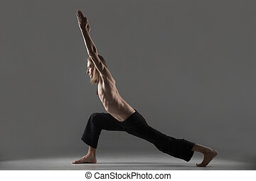 Variation of virabhadrasana 1 yoga pose - Sporty young man...