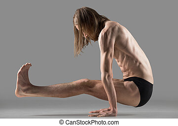 L sit yoga pose - Sporty young yogi man doing yoga pose for...
