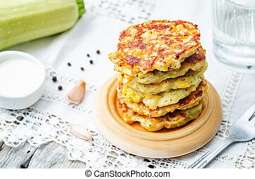 zucchini corn fritters on a white background. the toning....