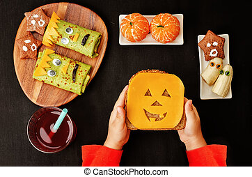 childrens hands holding sandwich in the form of monsters for...