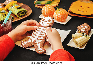 childrens hands holding cookies in the form of monsters for...