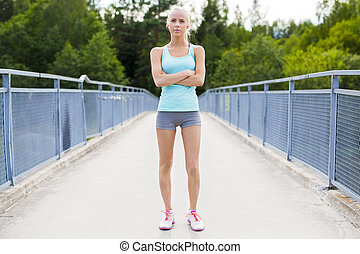 Confident young female runner having break after workout