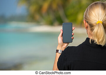 Woman hand showing a blank smart phone on the beach with the...