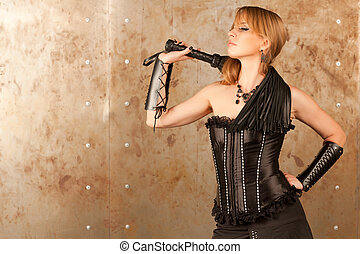 Woman and whip  - Beautiful woman in a corset holding a whip