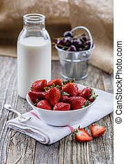 Strawberries in a Bowl with a Bottle of Milk - Fresh...