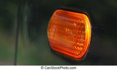 Turn signal light blinking on black car, traffic...