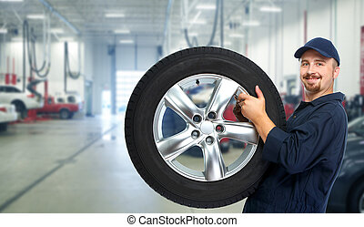 Car mechanic with a tire .