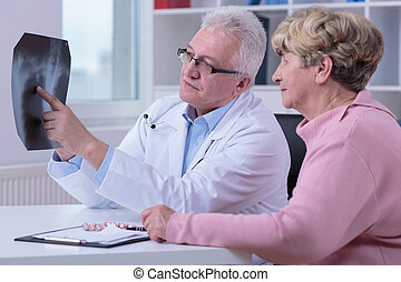 Pointing at x-ray image - Doctor is pointing at something on...