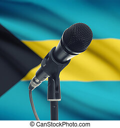 Microphone on stand with national flag on background -...