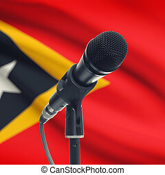 Microphone on stand with national flag on background - East...