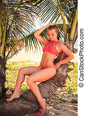 blond girl in bikini sits on palm smooths hair looks...