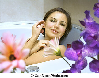 woman in a bath with flower petals - beautiful woman in a...
