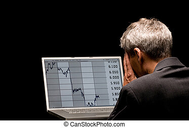 banking crises - desperated man with charts on his laptop