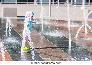 Splash park - Cute toddler girl playing with small fountains...