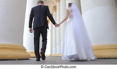 the bride and groom go among the columns