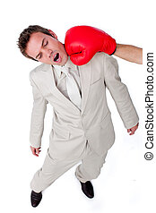 Attractive businessman being hit with a boxing glove...