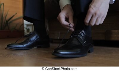 groom puts on shoes and tying shoelaces
