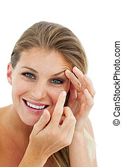 Smiling woman putting a contact lens isolated on a white...