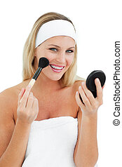 Delighted woman putting on make-up
