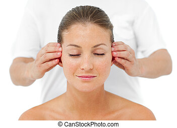 Charming woman having a head massage in a spa center