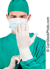 Self-assured surgeon wearing surgical gloves against a white...