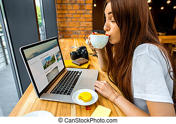 Woman working online with coffee cup - Young woman enjoying...