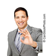 Charming businessman showing OK sign against a white...