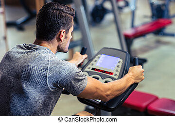 Man workout on a fitness machine - Young man workout on a...