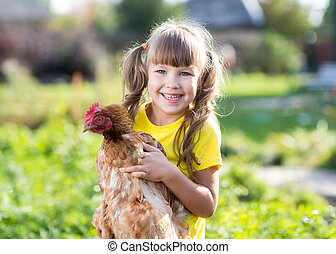 little girl with a hen in the front yard - smilimg little...