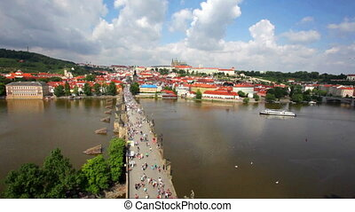 Crowded The Charles Bridge and Vltava river shore -...