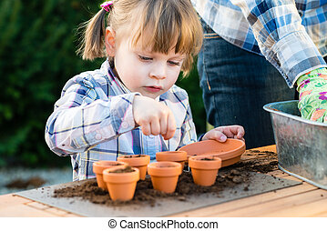 Girl planting flower seeds into pots with her mother - child...