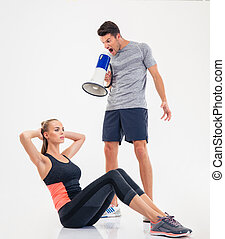 Trainer screaming through loudspeaker on a woman to doing...