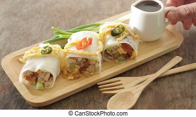 Serving spring rolls with vegetables on wooden plate