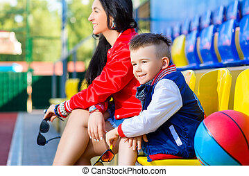 Rapper attitude rap singer hip Hop Dancer performing. Stylish woman and little boy posing at basketball court
