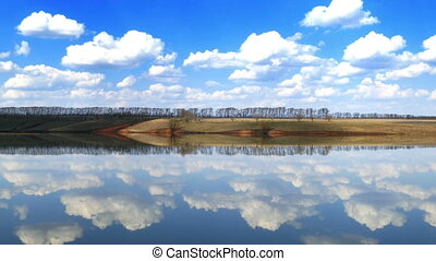Clouds are reflected in smooth water of lake, zoom in