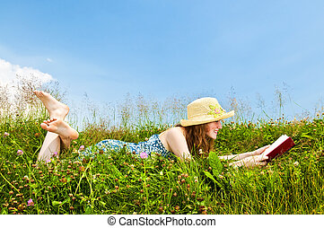 Young girl reading book in meadow - Young teenage girl...