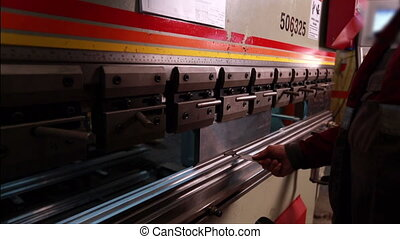 View of bending machine and worker holds fixture -...