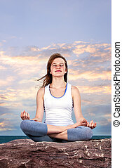 Young girl meditating at sunset - Portrait of young teenage...